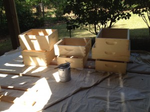 After assembling the hive bodies and supers, they are ready for painting; first with an oil based primer and then an oil based top coat. The joints have been sealed with caulk to ensure uniform painting and to prevent wood rot.