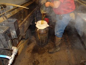 The boiling syrup is filtered in small batches before it is put in stainless steel drums